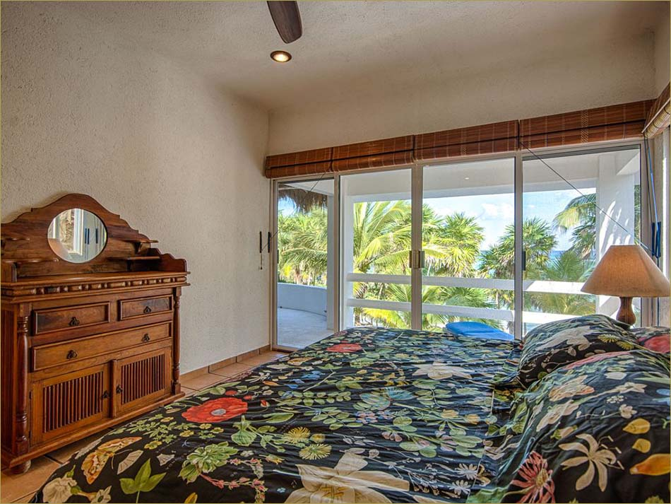 Master bedroom upstairs features a king sized bed, open balcony and private bathroom.